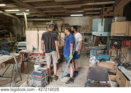 Team Of Carpenters Making Furniture In A Workshop