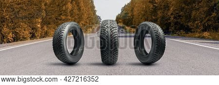 Three All-season Winter Or Autumn Tires On The Road In Autumn With Yellow Leaves. Preparing A Car Fo