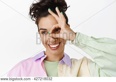 Smiling Brunette Woman Looking Aside At Logo, Shows Okay Ok Sign To Praise, Compliment Good Thing, A