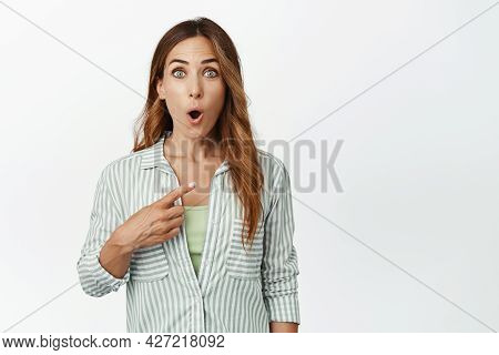 Portrait Of Surprised And Impressed Middle Aged Woman, Gasp Wow Face, Pointing Finger Right At Smth