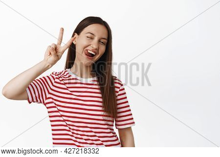 Happy Young Woman Wink, Show Tongue Silly And Peace V-sign, Positive Summer Mood, Wearing Striped Re