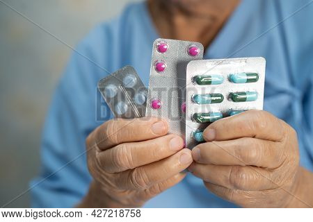 Asian Senior Or Elderly Old Lady Woman Patient Holding Antibiotics Capsule Pills In Blister Packagin