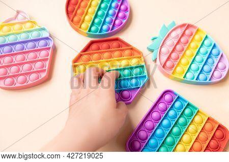 Hand Is Using Rainbow Push Pop It Bubble Sensory Fidget Toy, Sensory Silicone Toys For Autism, Fidge
