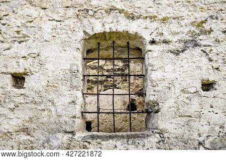 Arched Window With Metal Bars In Old Stonework. The Texture Of The Old Dilapidated Masonry. The Anci