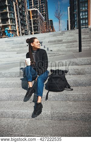 Joyous Lady With A Disposable Paper Coffee Cup Looking Away