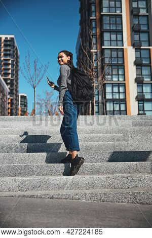 Joyous Tourist With A Backpack And A Cellphone Going Up The Stairs