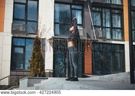 Serious Sportswoman Performing The Standing Torso Stretch Outside