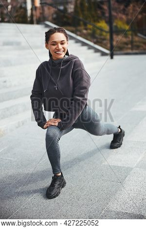 Sporty Lady With A Radiant Smile Performing A Warm-up Exercise