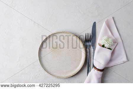 Beige Ceramic Plate, Cutlery And Napkin On A Beige Stone Table. Knife And Fork On Next To A Pink Nap