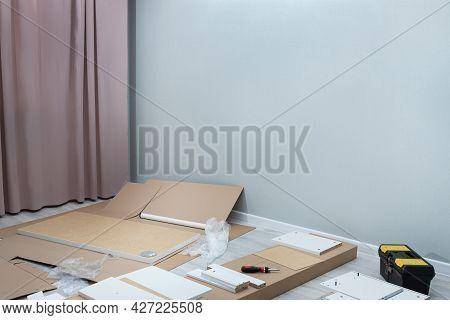 Relocation And Assembling Furniture Concept.unpacking A Cardboard Box With Furniture.assembly Of New