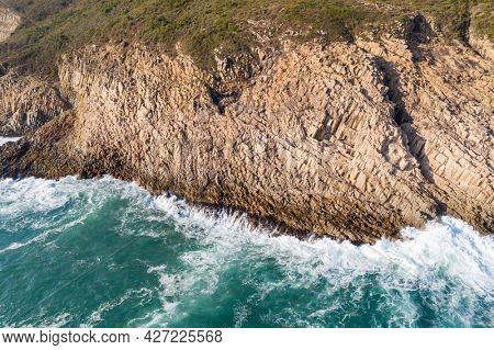 Ocean waves splash against rock on island