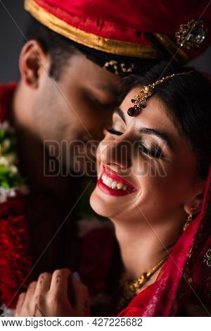 Blurred Indian Man In Turban Near Happy Bride In Traditional Headscarf Isolated On Grey