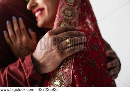 Cropped View Of Bridegroom With Golden Ring On Finger Hugging Happy Indian Bride In Headscarf Isolat
