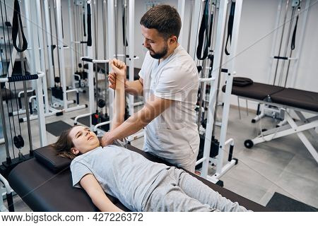 Girl Receive Shoulder Manual Therapy From Physiotherapist Man In Recovery Clinic. Sport Injury Rehab