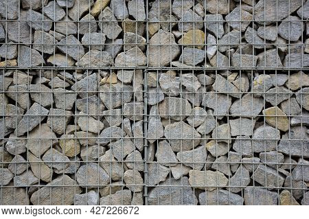A Large Fence Of Many Stone Cobblestones Supported By A Stone Trellis For The Entire Frame. The Desi