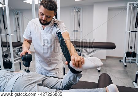 Pediatric Physiotherapist With Massaging Percussion Hammer Treats Girls Leg And Back With Espander
