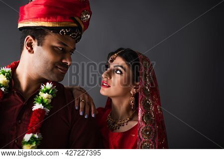 Indian Man In Turban Looking At Bride In Traditional Headscarf Isolated On Grey