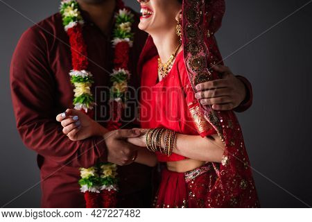 Cropped View Of Indian Man In Floral Garland Hugging Happy Bride In Traditional Headscarf Isolated O