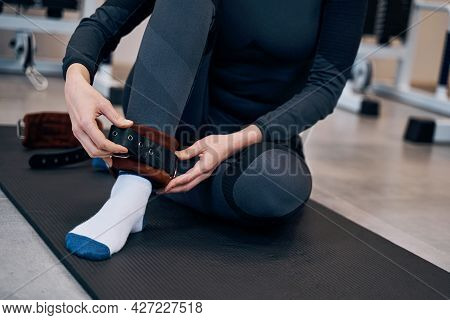 Pretty Caucasian Woman In Black Sportwear Wearing Cuffs Of Ankle Support. Protection And Anti-sprain