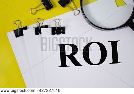 Return On Investment Concept Word Written On White Paper And Yellow Background With Magnifier