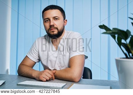 Portrait Of Male Physician With Self-confidence At Private Clinic Office. Interior Of Workplace