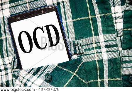Obsessive Compulsive Disorder Word Written On The White Screen Of The Phone That Lies In The Shirtr