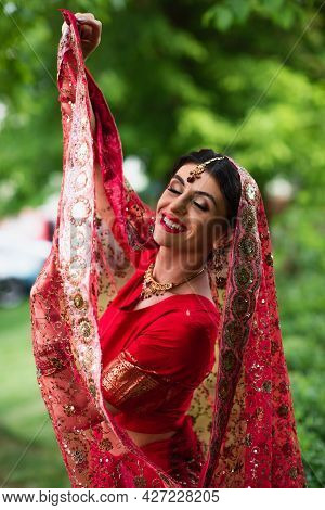 Joyful Indian Bride In Red Sari Holding Traditional Headscarf With Ornament
