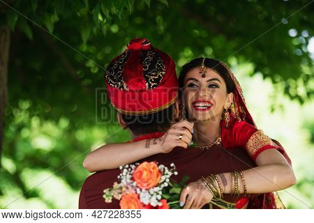 Back View Of Indian Man In Turban Hugging Cheerful Bride In Traditional Headscarf Holding Flowers