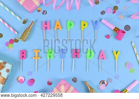 Letter Canles Forming Text Happy Birthday With Confetti And Paper Streamers On Blue Background