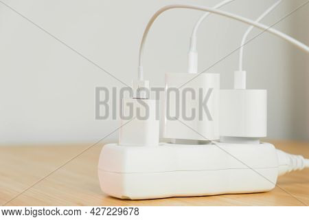 The Electrical Extension Strip With Connected White Power Plugs On The Wooden Table. Smartphones Cha
