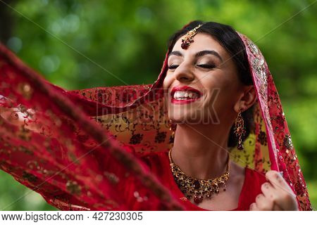 Positive Indian Bride In Red Sari Adjusting Headscarf With Ornament