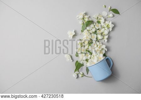 Floral Composition On Gray Background With Green Leaves, Flowers In  Cup Flat Lay. Spring Floral Bac