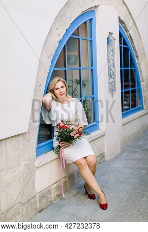 Stylish Mature Lady In White Elegant Dress Posing At Camera With Flower Bouquet Outdoors In The City