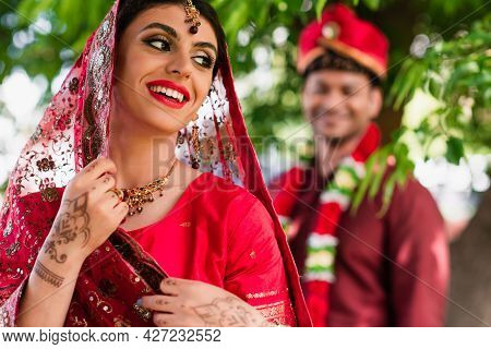 Happy Indian Bride In Sari And Headscarf Near Blurred Man In Turban On Background