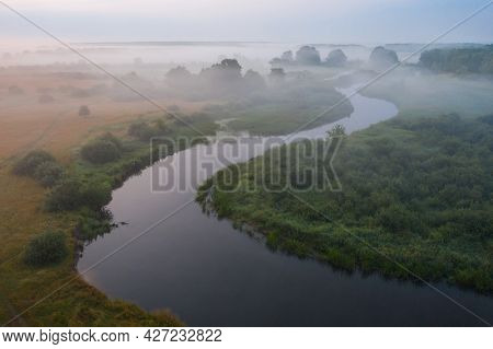 Aerial View Of Winding River. Misty Sunrise Above The Meadow. Beautiful Landscape Of Nature.