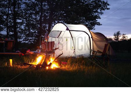 Summer Camping. Traveling With A Tent. Campfire Sunset. Different Things And Folding Chairs Near The