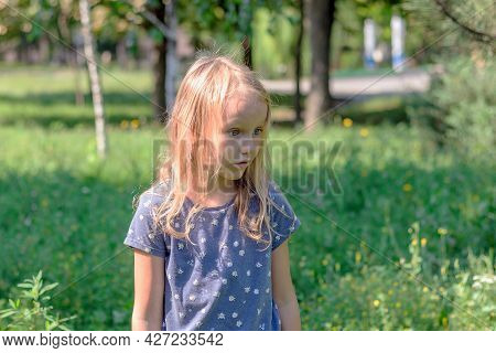 Little Girl, Blonde Six Years Old, With A Very Surprised Face, Against The Background Of Nature, Por