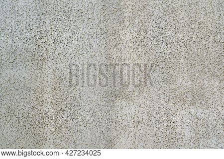 Fragment Of A Wall Of A Building Covered With Gray Plaster. The Surface Has A Pronounced Relief Of S