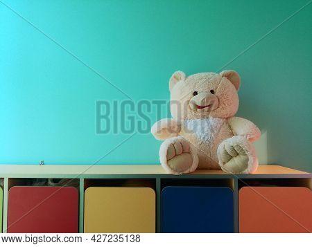 Cute Plush White Bear Sitting On A Colorful Vivid Preschool Kindergarten Lockers. Back To School Con