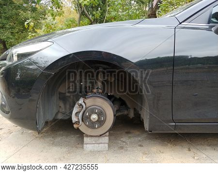 Car Standing On A Bricks With Stolen Wheel. Depict Insurance From Criminal Issues