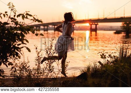 Women Running At Sunset. Lifestyle Full-length Portrait Of A Beautiful Young Woman In A Long White D