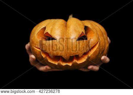 Hands Holding A Traditional Halloween Creepy Carved Pumpkin (jack O Lantern) On Black Background. Ha
