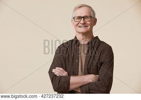 Minimal Waist Up Portrait Of Senior Man Wearing Glasses And Looking At Camera While Standing With Ar
