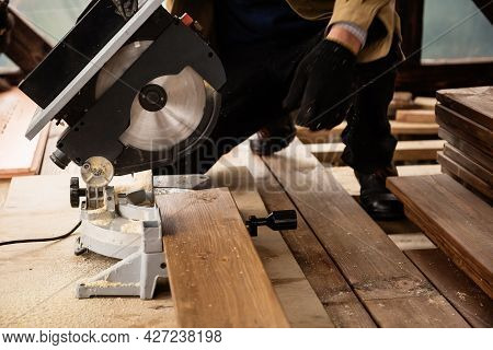 Miter Saw With A Large Metal Blade In The Hands Of A Carpenter. Working Tool For Sawing Wooden Plank