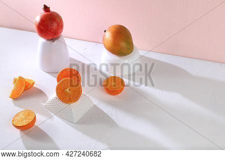 Modern Still Life With Citrus, Orange Juice And Oranges, Pomegranate And Mango On Stand And Podiums