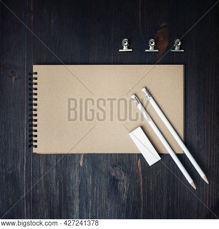 Photo Of Closed Blank Kraft Sketchbook, Pencils And Eraser On Wood Table Background. Template For Pl