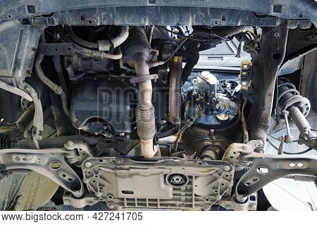 Modern Car In A Car Service On A Lift. Bottom View Of Engine, Gearbox Removed. Flywheel, Exhaust Pip