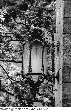 Exterior Light Fixture Mounted On Wall With Designed Details Against A Blurry Background With Foliag