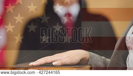 American flag design against mid section of woman taking an oath in the court room. american law and justice concept