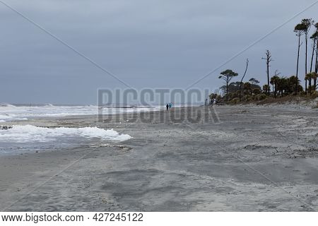 Distant Walkers Along The Shoreline During A Storm, Heavy Seas And Foam, Horizontal Aspect